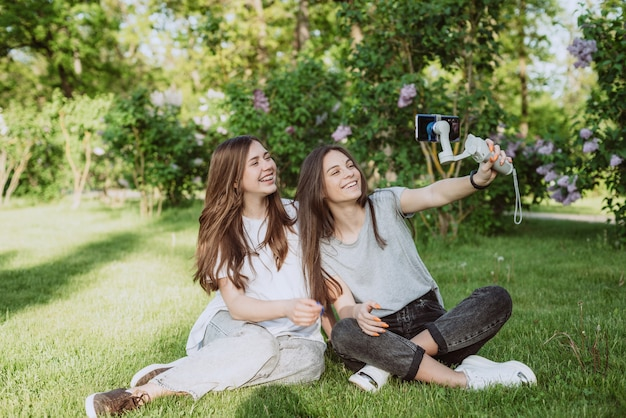 Smiling pretty young women influencer bloggers are filming or recording video with their smartphone on a stabilizer, in a sunny green park outside. blogging concept. soft selective focus.