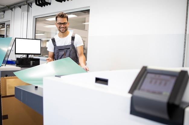 인쇄소에서 기계를 도금하기 위해 컴퓨터를 작동하는 웃는 인쇄 작업자.