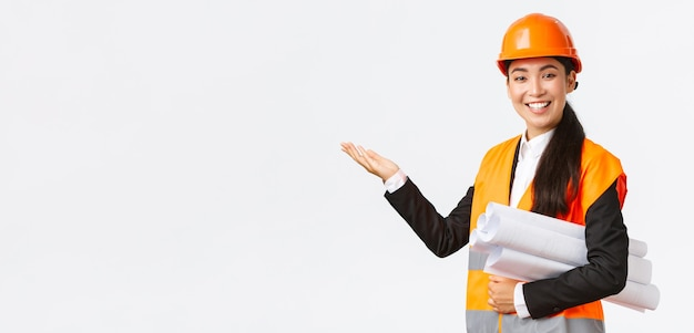 笑顔のプロのアジアの女性建築家、安全ヘルメットのエンジニアが建設プロジェクトを紹介し、青写真を運ぶように左手を指して、スピーチをし、チャートや建物の計画を紹介します