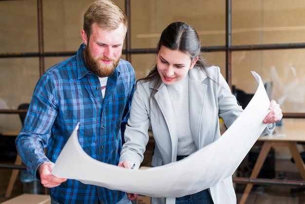 Smiling professional businesspeople working on blue print