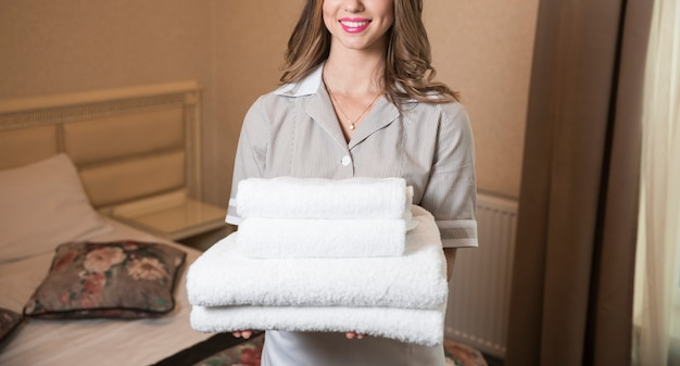 Smiling professional chambermaid holding pile of clean towels in bedroom