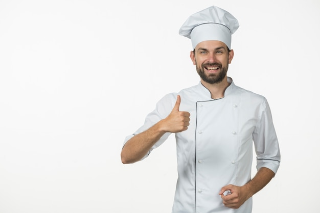 Smiling professional cook showing thumb up sign against white backdrop