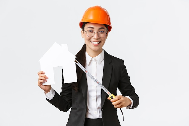 Smiling professional female asian engineer, architect in helmet and business suit showing house maket and tape measure, ready starting home renovation, construction works, white background