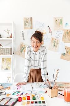 Улыбается профессиональная женщина дизайнер, опираясь на свой рабочий стол