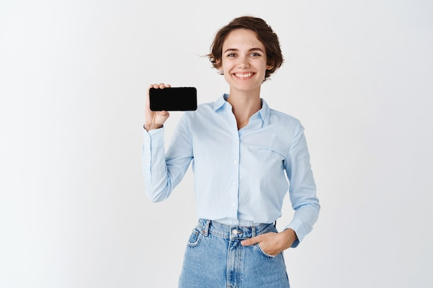 Smiling professional woman holding smartphone screen horizonally, demonstrate application, standing on white wall