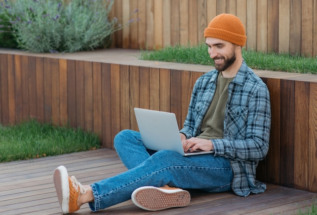 自宅で仕事をしているラップトップコンピューターを使用して笑顔のプログラマー