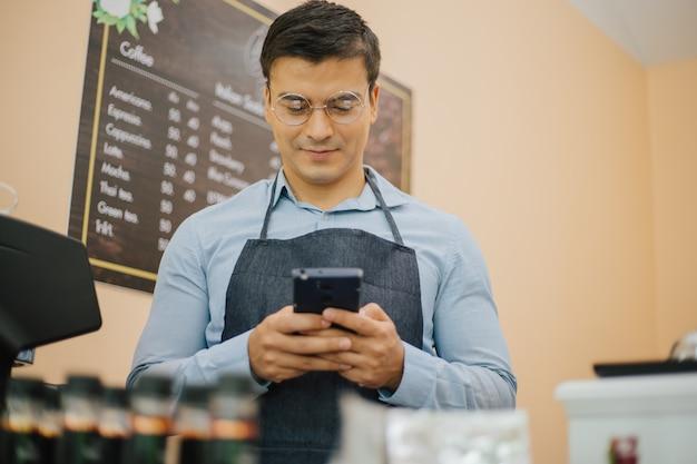 Улыбающийся преуспевающий мужчина-владелец малого бизнеса возле бара, проверяющий почту на мобильном телефоне