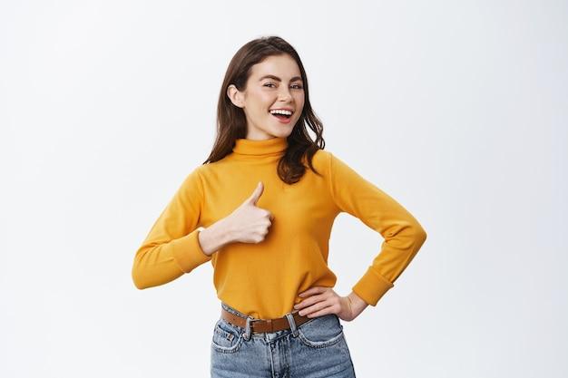 Sorridente donna orgogliosa che mostra il pollice in su e dice di sì, annuisce per accettare o approvare, lodando il buon lavoro o la buona scelta, in piedi contro il muro bianco