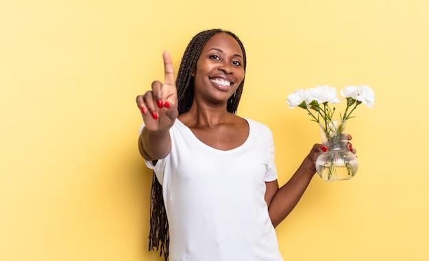 誇らしげに自信を持って笑顔でナンバーワンのポーズをとって、リーダーのように感じます。装飾的な花のコンセプト