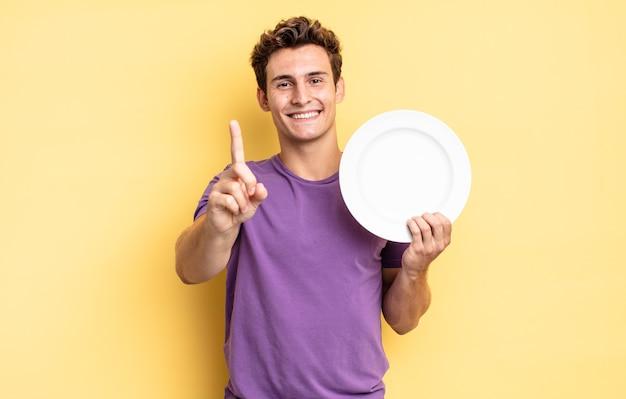 Гордо и уверенно улыбаясь, триумфально принимая позу номер один, чувствуя себя лидером. концепция пустой тарелки