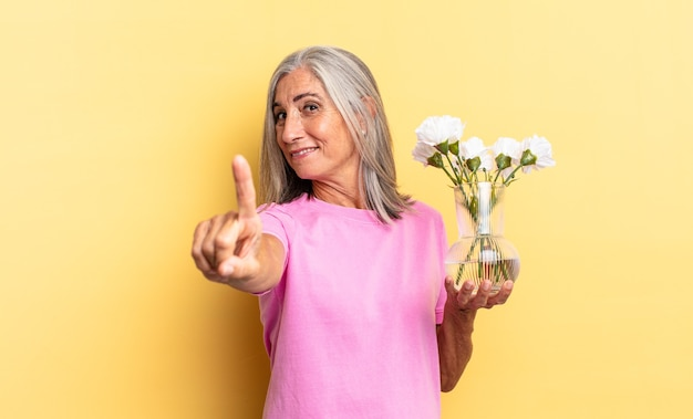 의기양양하게 웃고 당당하게 1위 포즈를 취하며 장식용 꽃을 들고 있는 리더의 기분
