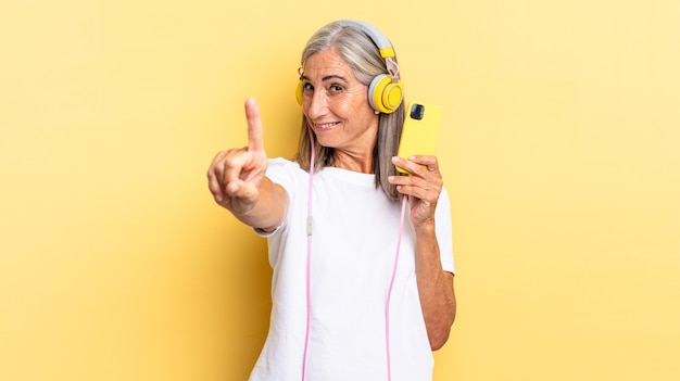 Smiling proudly and confidently making number one pose triumphantly, feeling like a leader with headphones