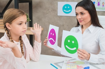 Smiling psychologist showing happy and sad emotion faces cards to the girl child