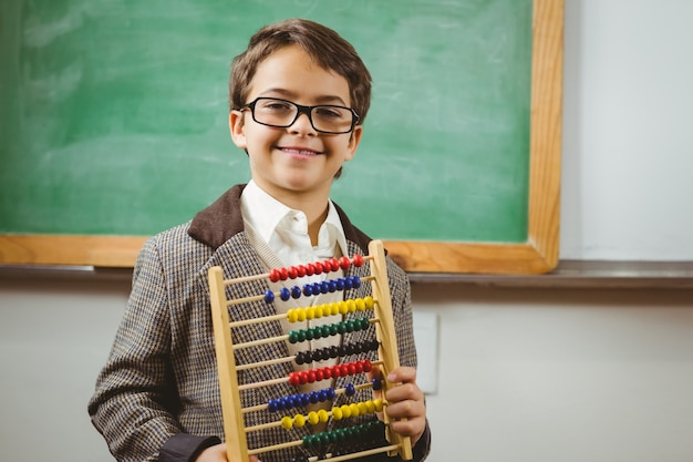 Smiling pupil dressed up as teacher holding abacus