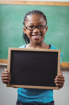 Smiling pupil holding chalkboard in a classroom