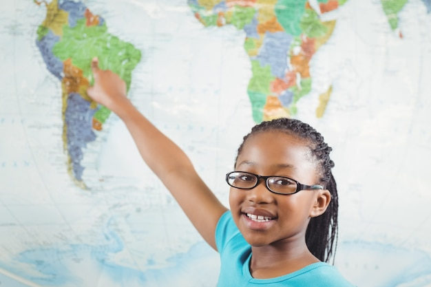 Smiling pupil pointing on world map in a classroom