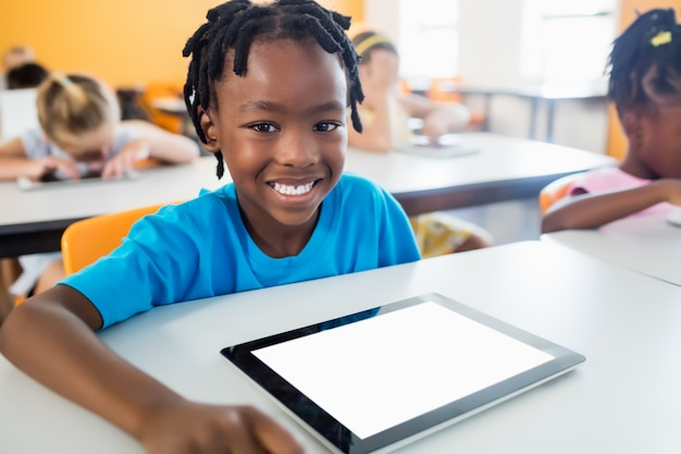 Smiling pupil posing at desk with tablet pc