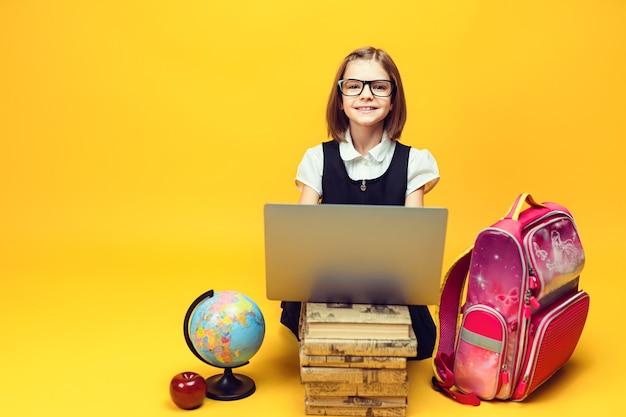 웃는 학생은 책 더미 뒤에 앉아 있고 지구본이 있는 노트북은 카메라 어린이 교육을 봅니다.