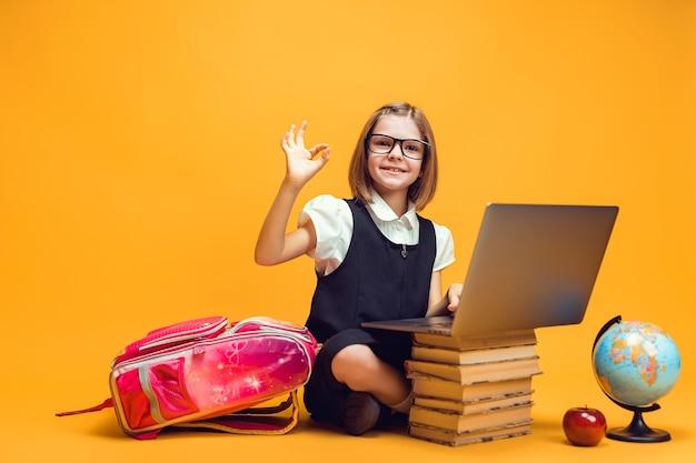 웃는 학생은 노트북이 있는 책 더미 뒤에 앉아 손으로 노래하는 어린이 교육을 보여줍니다.