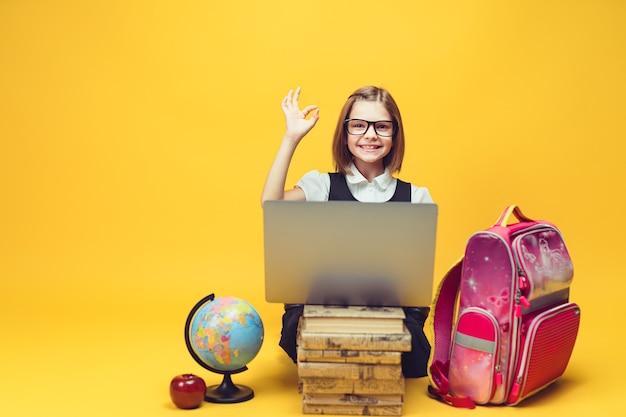 책 더미 뒤에 앉아 있는 웃고 있는 학생과 확인하는 손 노래를 보여주는 노트북