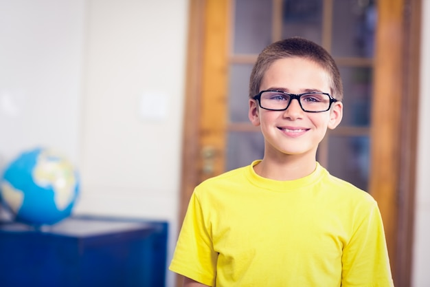 Smiling pupil wearing glasses in a classroom