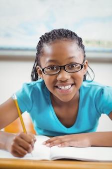 生徒は机の上で机で働いて笑顔で