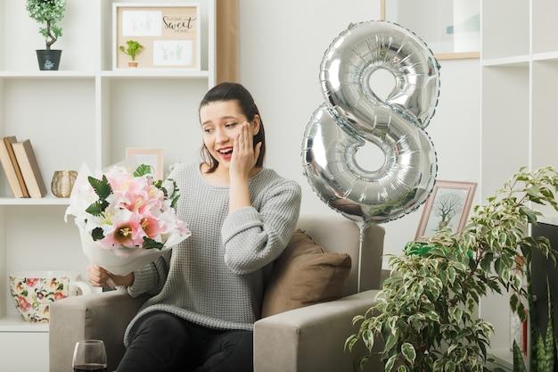 Sorridente mettendo la mano sulla guancia bella ragazza il giorno delle donne felici che tiene il mazzo seduto sulla poltrona in soggiorno