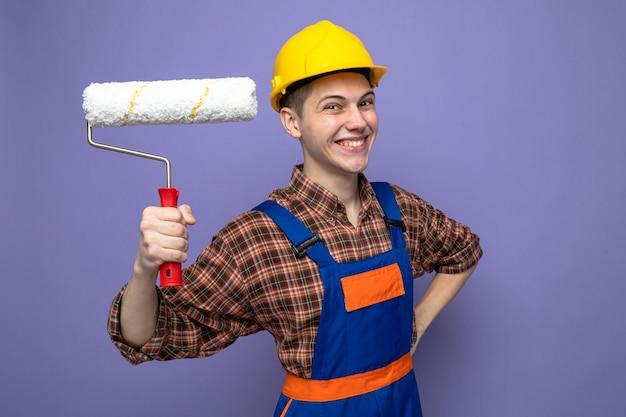 Sorridente mettendo la mano sull'anca giovane costruttore maschio che indossa l'uniforme tenendo la spazzola a rullo