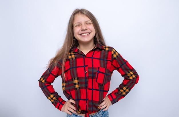 Sorridente mettendo le mani sull'anca bella bambina che indossa una maglietta rossa