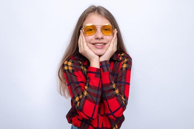 頬に手を置いて笑顔白い壁に隔離の赤いシャツとメガネを身に着けている美しい少女