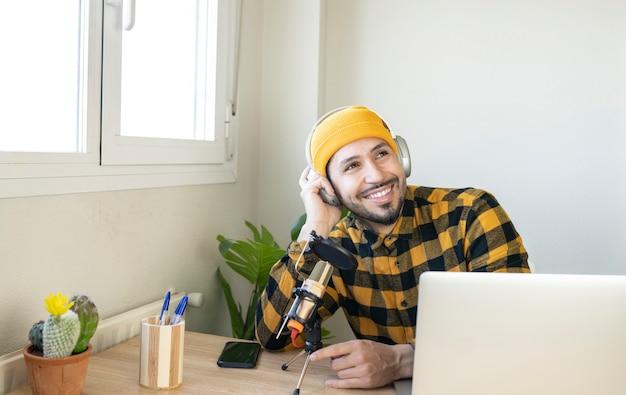 마이크와 헤드폰을 들고 사무실에 앉아 웃고 있는 라디오 진행자