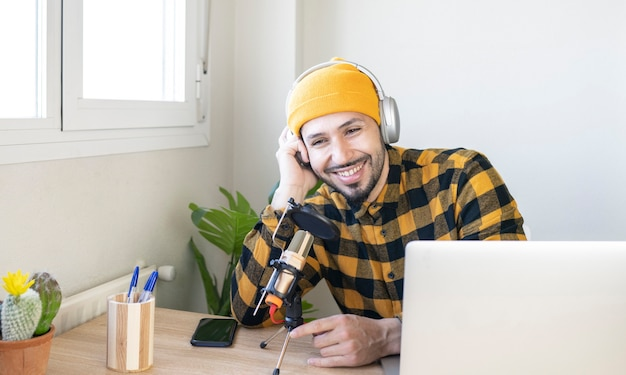마이크와 함께 사무실에 앉아 웃는 라디오 호스트