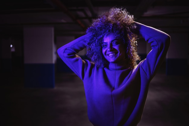 紫色のライトの下で地下ガレージでポーズをとってカメラを見ている笑顔のラップの女の子。