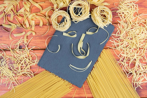 Smiling raw pasta on wooden background.