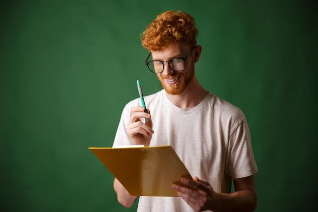 Uomo barbuto sorridente del readhead nella cartella e nella penna bianche della tenuta della maglietta