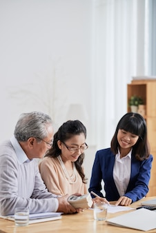 Smiling real estate agent asking senior couple to sign document after they pay deposit for house