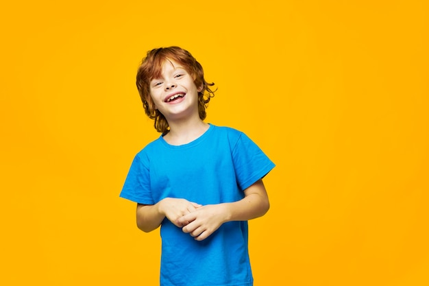 笑顔の赤い髪の少年楽しい子供時代の青いtシャツ黄色