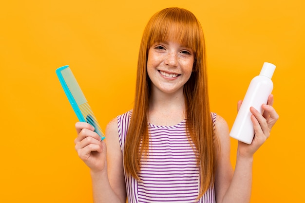 Smiling red-haired girl combing her hair and holding a shampooon over yellow background