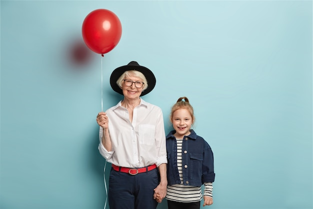 Smiling red haired girl comes to congratulate granny with mothers day, wears striped jumper and denim jacket. glad senior lady in stylish black hat, carries balloon, holds hand of small granddaughter