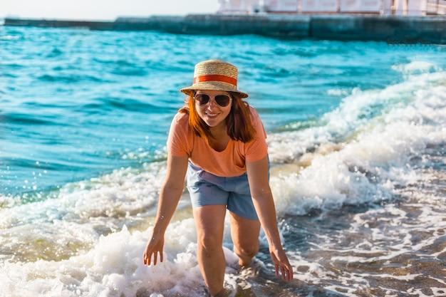 海で帽子、ショートパンツ、tシャツで赤い髪の少女の笑顔。
