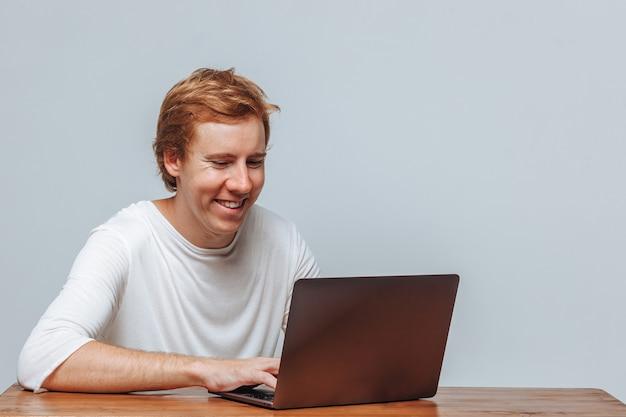 Улыбающийся рыжеволосый программист на светлом фоне для ноутбука
