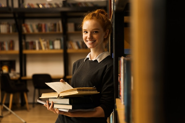 Smiling red haired teenage girl carrying books