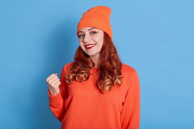 笑顔の赤い髪の女性は拳を食いしばり、赤い口紅を着て、カジュアルなジャンパーと帽子を着ています