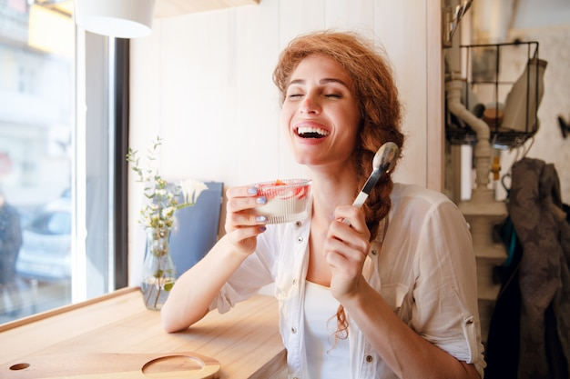 Smiling red haired woman sitting in cafe and eating dessert