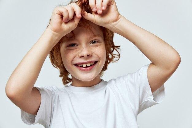 彼の頭の近くで手をつないでいる赤毛の少年の笑顔笑顔白いtシャツ