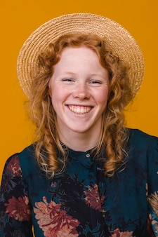 Smiling redhead female in studio with bright background