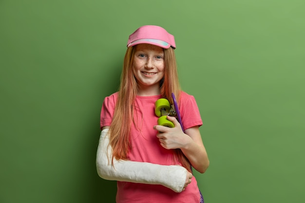 Smiling redhead girl had accident after riding skateboard, wears cast or plaster on broken arm, stays happy, got injured during favorite sport, stands against green wall. children, health care
