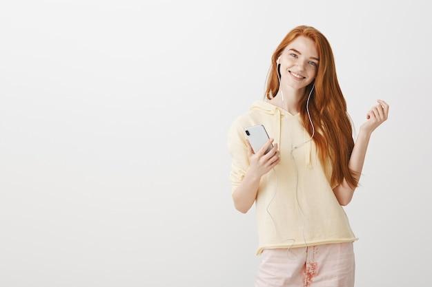 Улыбающаяся рыжая девушка слушает muisc в наушниках и держит смартфон