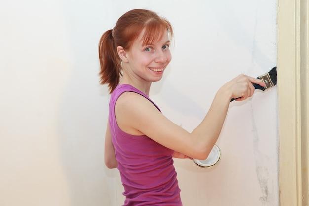 笑顔の赤毛の女の子がアパートの修理中に白い壁をペイントします