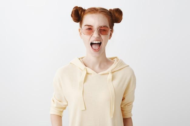 La ragazza sorridente della testarossa in occhiali da sole strizza l'occhio spensierata